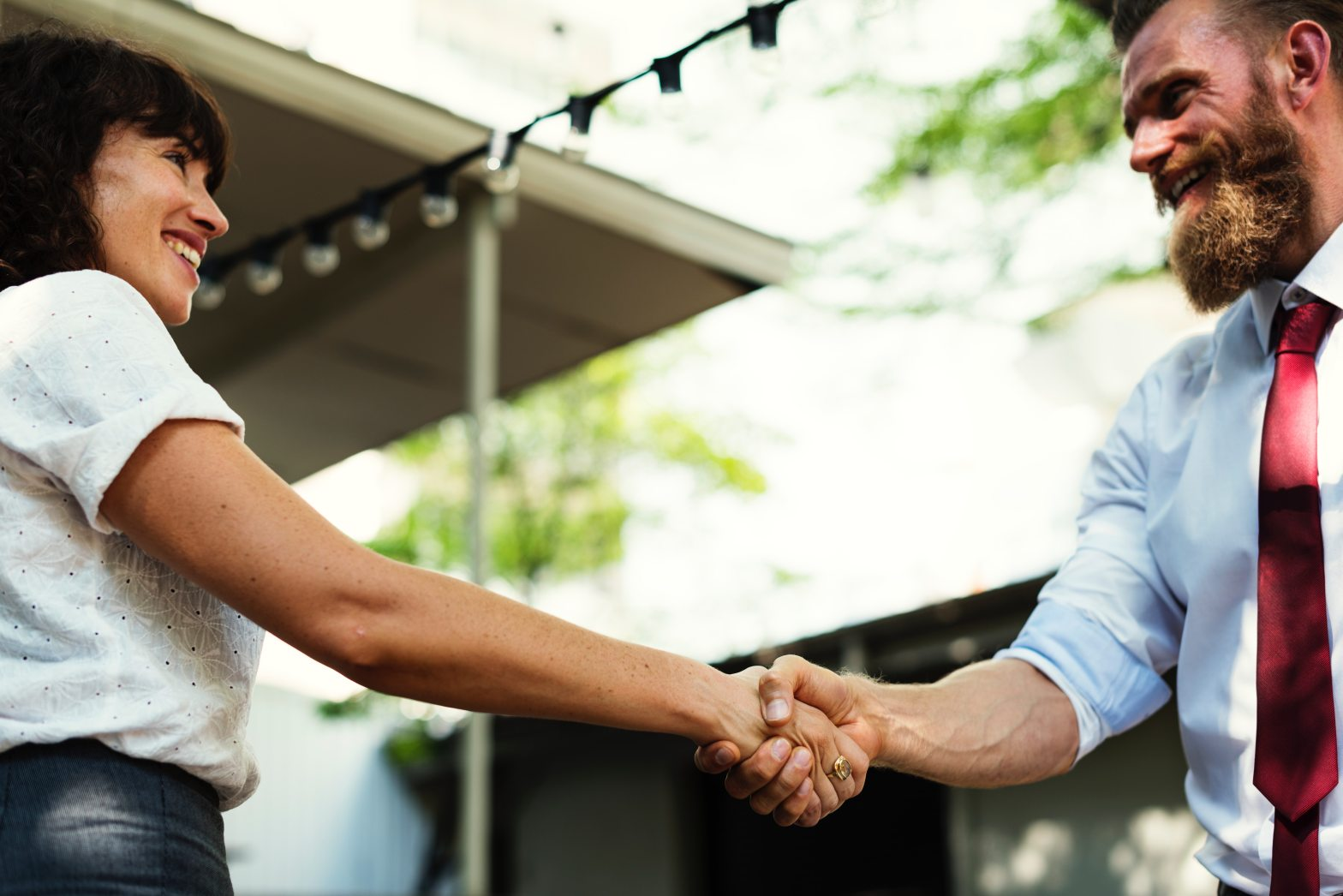 man and woman shake hands after negotiating